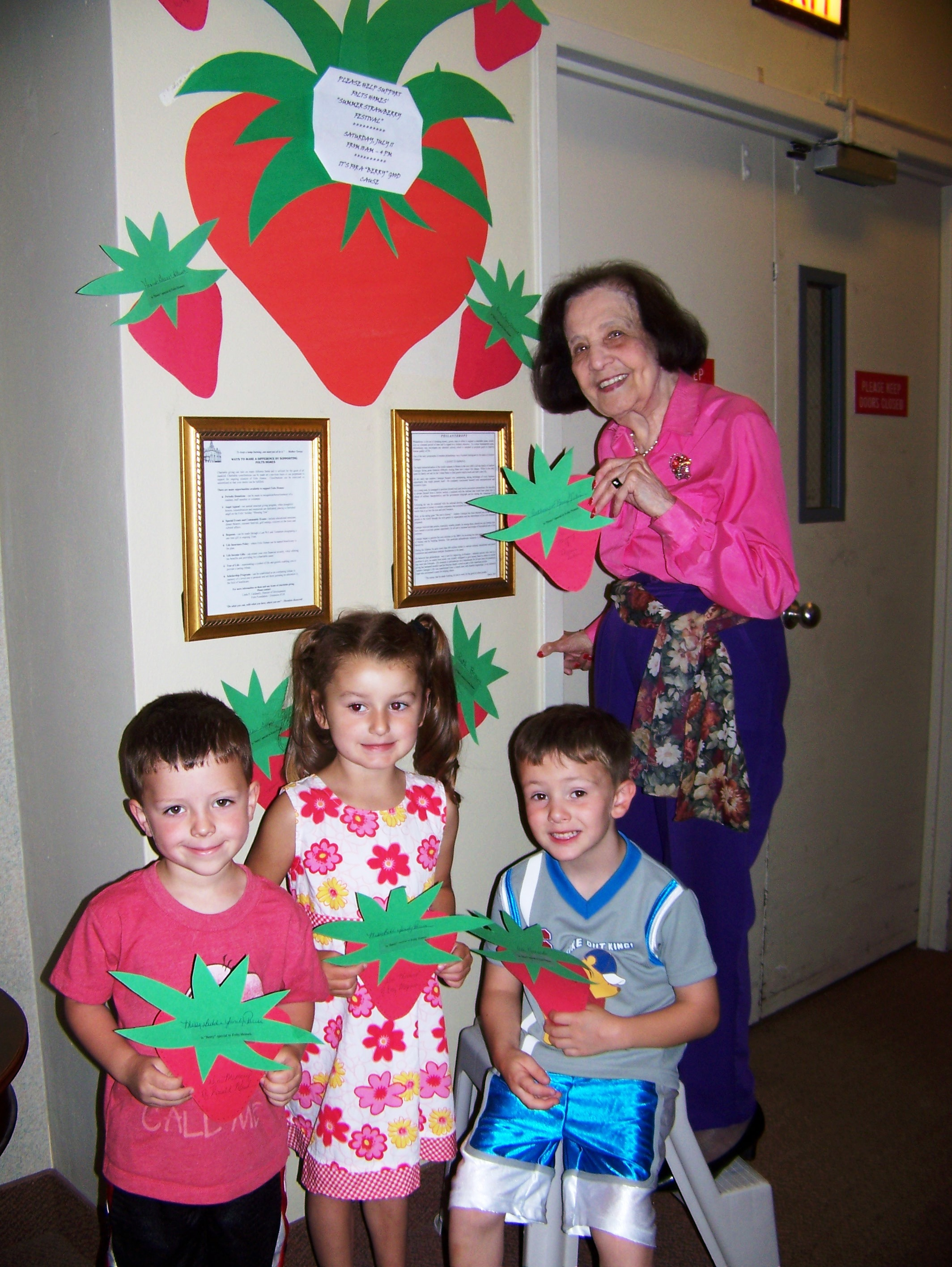 Shown decorating Folts Homes for the upcoming �Summer Strawberry Festival� are children from the Child Daycare Center, from left, Trey Dillion, Lauren Jory and Quintin Miller with Claxton Manor resident Ida Guzzo, who organized a paper strawberry sale in support of the event